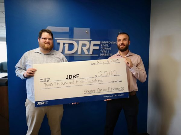 Source employee and JDRF employee holding a giant check