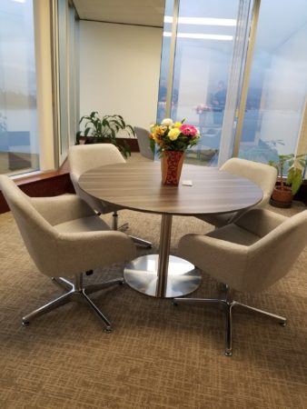 Source Vancouver's design at the Cinec Education Group Canada office. Round office table with four chairs around it and flowers on top of the table.
