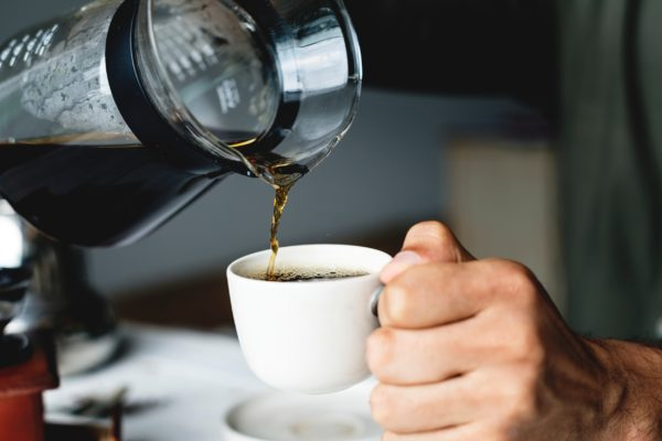 Person holding a cup and pouring coffee into it